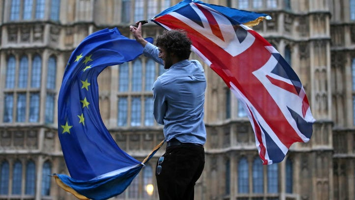 A man waves both a Union flag and a European flag together