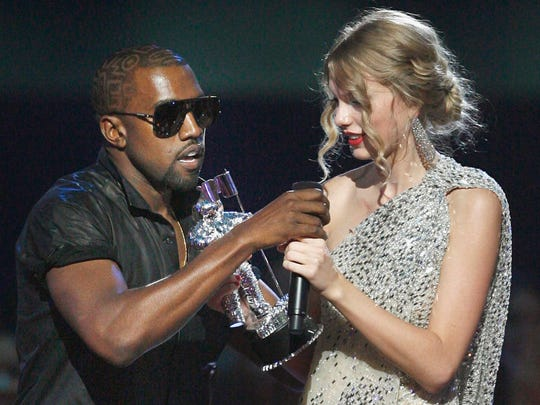 """Kanye West takes the microphone from Taylor Swift as she accepts the """"Best Female Video"""" award on Sept. 13, 2009, during the MTV Video Music Awards in New York."""