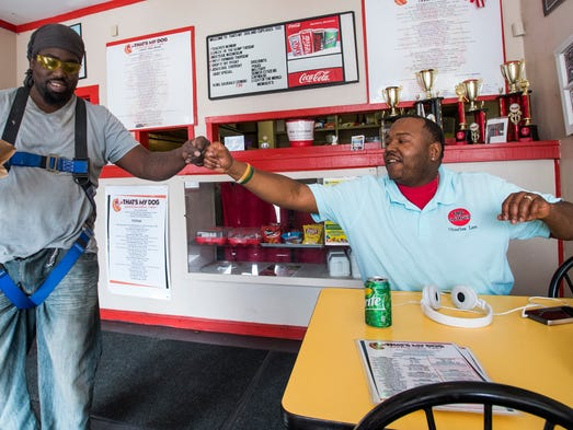 Charles Lee fist bumps a customer at his restaurant,