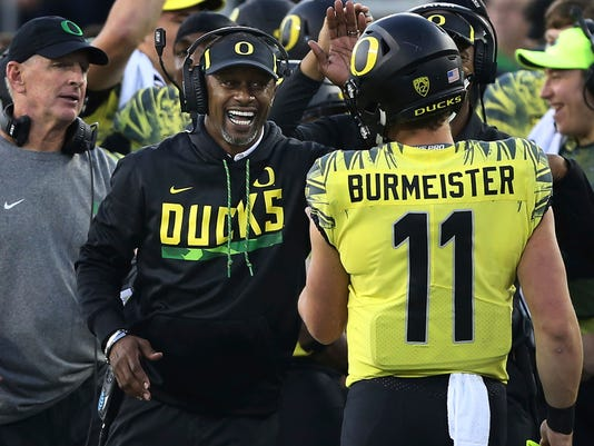 FILE - In this Oct. 28, 2017, file photo, Oregon head coach Willie Taggart congratulates Oregon quarterback Braxton Burmeister after an Oregon score against Utah in the fourth quarter of an NCAA college football game in Eugene, Ore. Oregon and Oregon State head into the 121st Civil War game in Eugene, on Saturday, Nov. 25, 2017, looking very different than last season. (AP Photo/Chris Pietsch, file)