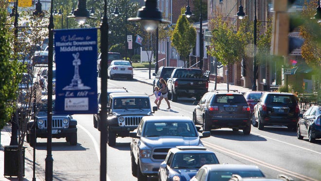 A pedestrian crosses Main Street as traffic backs up during rush hour in Middletown on Sept. 8. The Appoquinimink School District is dealing with a sharp increase in enrollment because of population gains in the area.