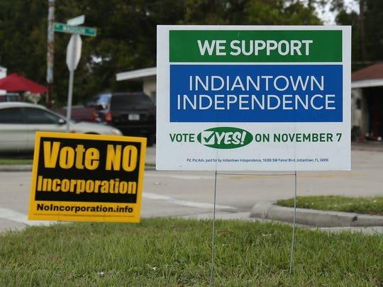 Competing signs are seen in Indiantown on Oct. 10, 2017.