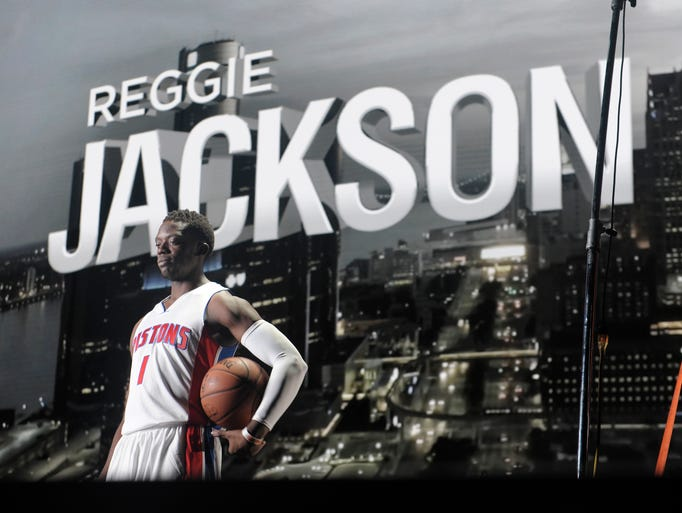Reggie Jackson poses in front of a backdrop of downtown