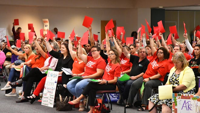 During the presentation of the Marjory Stoneman Douglas High School Public Safety Act, some members of the audience held up red sheets of paper when district staff talked about putting guns in schools and held up green sheets of paper when they talked about more mental health services for students.