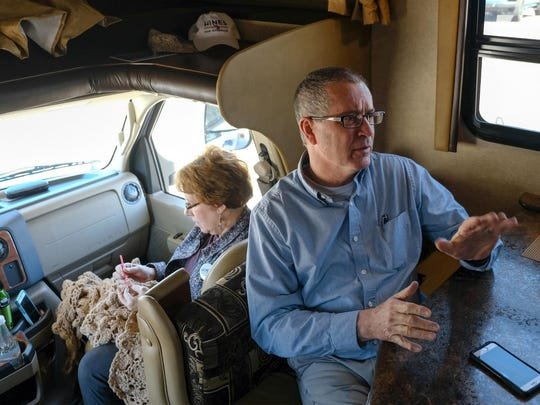 Republican gubernatorial candidate Dr. Jim Hines, a Saginaw physician, talks about the race ahead in his mobile campaign vehicle while parked in Saginaw on Friday, April 20, 2018, as his wife, Martha Hines, crochets while sitting behind him.