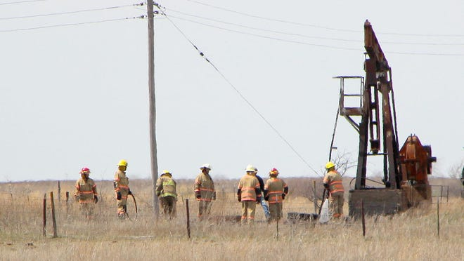 Preston firefighters check for hot spots near an oil pumper about two miles north of Natrona on April 1. Only weeds were burned in the fire of undetermined origin.
