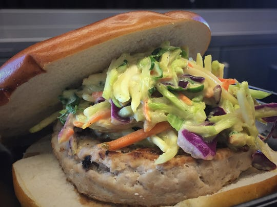 Jalapeno coleslaw tops a turkey burger on a pretzel