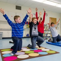 From left, second-grade Candor Elementary School students, Gavin Wood, Keydan Finch, Mathaius Vanzile, and Corbyn White demonstrate a set of yoga exercises taught to them and other teachers in the school by occupational therapist Danielle Banks, back.