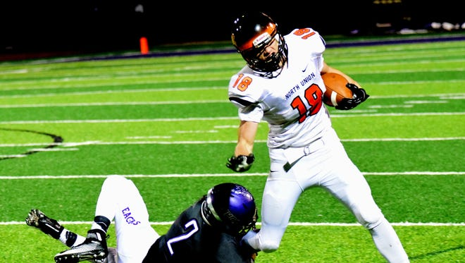 CHCA's Brady Pfister (2) holds on to North Union's Nate Hammon's (18) and brings him down after short gain during a Division V playoff football game last year. More playoff games will likely be moved to Friday nights starting next season.