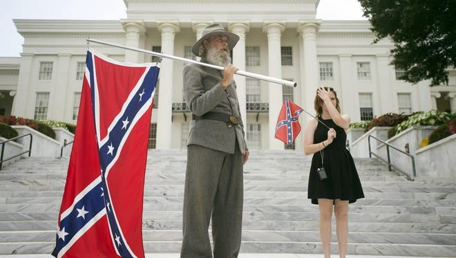 Dan Williams, 65, of Ashville, Ala., holds a Confederate flag while standing with his daughter Bonnie-Blue Williams, 15, in front of the Alabama state Capitol building during a Confederate flag rally on Saturday in Montgomery, Ala.