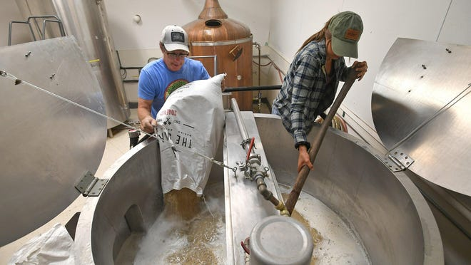 Brian Sprague, at left, and intern Emma Guzik, 20, begin the brewing process on June 3 at Sprague Farm & Brew Works in Cambridge Township, Crawford County. Sprague, 61, co-owner of the craft brewery, adds grain to a vat, called a mash tun, of hot water. It was the first step in the brewing of eight barrels or about 250 gallons of Ale Mary, one of the regular brews at Sprague Farm & Brew Works.