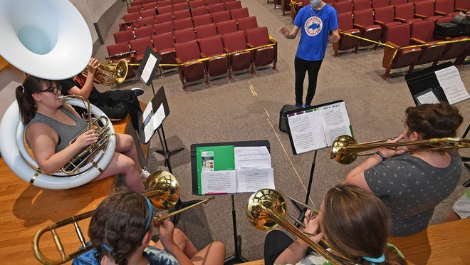 The Fort LeBoeuf Marching Band low brass section rehearses Wednesday in the auditorium at Fort LeBoeuf High School in Waterford. Seated at left is sousaphone player Erin Lewis, 16. Leading the rehearsal (in blue T-shirt) is baritone horn player Sean Solt, 18. The 50-member band and color guard are taking extra precautions during their practices to slow the spread of COVID-19.
