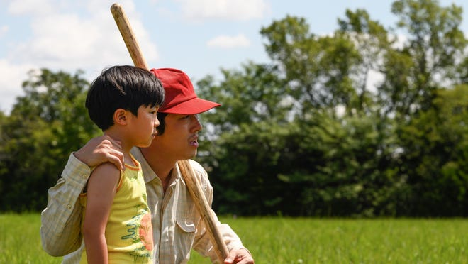 "Alan S. Kim, left, and Steven Yeun in a scene from ""Minari."""