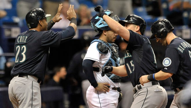 Seattle Mariners' Nelson Cruz (23) and Willie Bloomquist, right, greet Kyle Seager (15) at the plate after Seager's grand slam off Tampa Bay Rays reliever Jake McGee during the eighth inning of a baseball game Tuesday, May 26, 2015, in St. Petersburg, Fla.