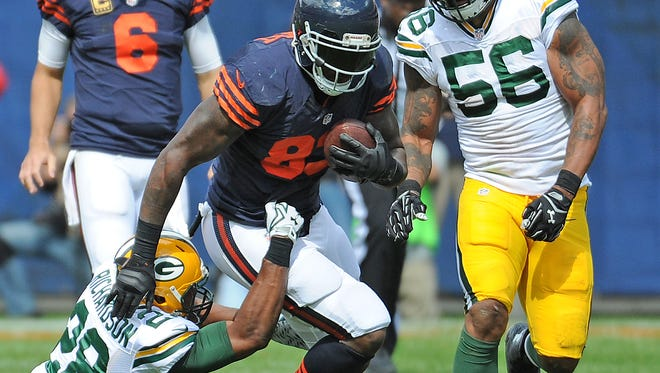 Packers safety Sean Richardson, lower left, and linebacker Julius Peppers (56) converge on tight end Martellus Bennett (83) against the Chicago Bears on Sept. 13.