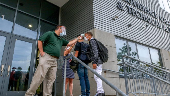 School nurse Michael Force and Assistant Principal Judy Fried check students' temperatures as they enter on Monday for the first day of school at Providence Career & Technical Academy.