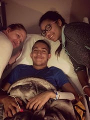 Thomas Harris lies in a hospital bed with his mother, Kim Kaletka, to his left and his sister Lexi to his right.