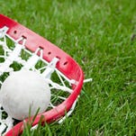 Girls lacrosse head and grey ball on grass