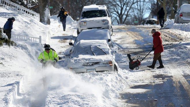 People clear snow Monday, Feb. 2, 2015, along Auburn Street in Dubuque.