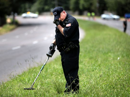 Memphis CSI Officer Eric Carlisle searches the median