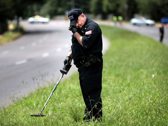 Memphis CSI Officer Eric Carlisle searches the median strip for bullet casings Monday afternoon near the scene where a 2-year-old girl was was shot in the head on Kirby Parkway following a dispute between her mother and another driver.