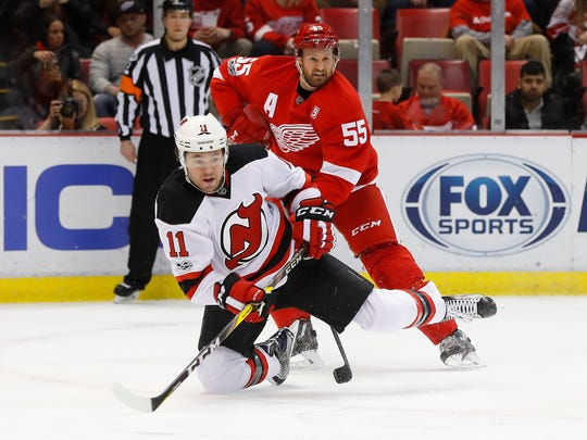 Devils right wing PA Parenteau (11) shoots as Red Wings defenseman Niklas Kronwall (55) defends in the first period Tuesday at Joe Louis Arena.