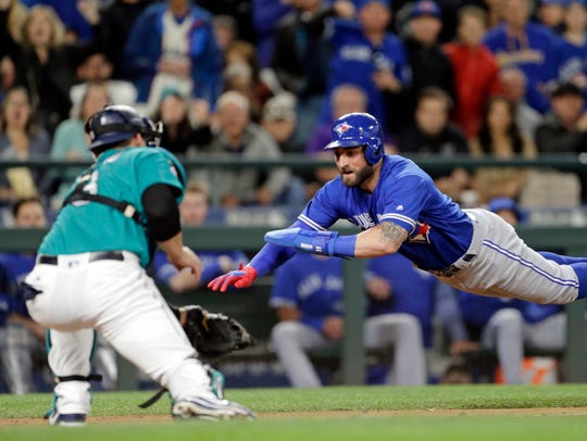Kevin Pillar of Toronto dives for the plate but is