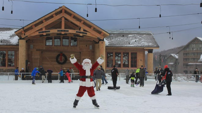 Santa Claus helps celebrate Saturday's opening of a new ice skating rink at Spruce Peak Village Center in Stowe.