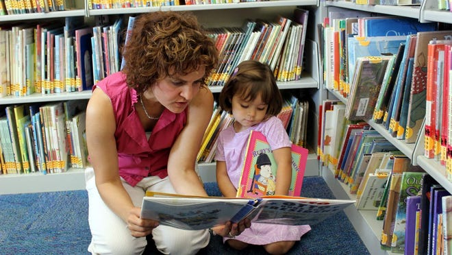Ava Sciolino and her mom, Alisa, from Irondequoit, enjoy a book at the Pittsford Community Library.