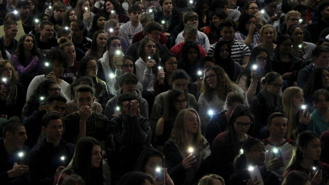 Students hold their lighted cellphones at a rally at Parkland High School outside Allentown, Pa., on Wednesday, March 14, 2018. Hundreds of students at Parkland walked out of class and headed to the auditorium for the #parklandforparkland rally, which was held to protest gun violence in response to last month's massacre of 17 people at Marjory Stoneman Douglas High School, in Parkland, Fla. (AP Photo/Michael Rubinkam)