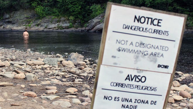 In this Wednesday, July 11, 2018 photo a swimmer wades in the Lehigh River at Lehigh Gorge State Park in Jim Thorpe, Pa. Two recent drownings in this stretch of the river highlight the hot-weather hazard posed by Pennsylvania rivers and streams. (AP Photo/Michael Rubinkam)