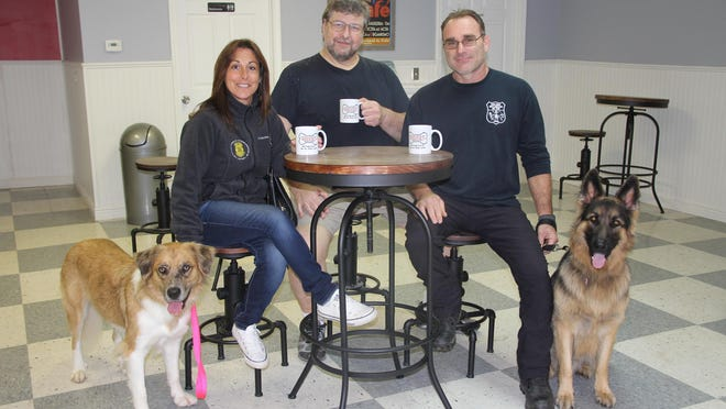 Christine Hillegeer, with Lucy, left, Rich Ackerman, center, and Jim Hillegeer, with Louie, at the new Coffee and Canines café in Parma. Ackerman and his wife, Cindy, also own Woofies, which is adjacent to the new café.
