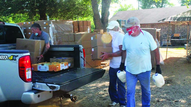 """Jimmy King, Roy Allen Reynolds, and Virgil Wells load food into the back of a pickup truck during a """"pop up pantry"""" at Trinity Pentecostal Church of God in Magazine Friday. The church received 1000 boxes of food from Go Fresh to distribute in addition to its typical Friday food pantry."""
