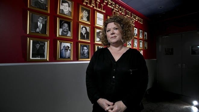 Margie Coyle, co-owner and manager of Cap City Comedy Club, in front of the wall of photos of Funniest Person in Austin winners in 2015.