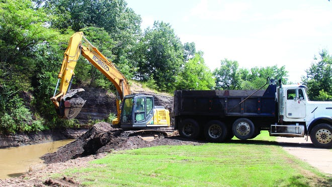 A backhoe operator is set to transfer a scoop of shale and dirt from the Booneville Creek bottom at Veterans Park to a waiting dump truck.