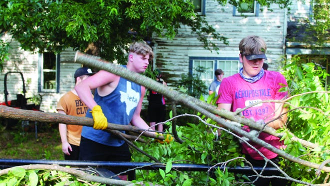 """Cameron Raggio (left) and William King load brush onto a trailer during a cleanup project at the """"Smith House"""" on Highway 10 in Magazine last week."""