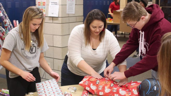 Student Senate adviser Cathy Engel helps students wrap presents for the West Ottawa Student Senate annual toy drive on Dec. 7, 2019. For this year's drive, students were unable to physically collect and wrap presents and instead turned to online shopping to continue the tradition.