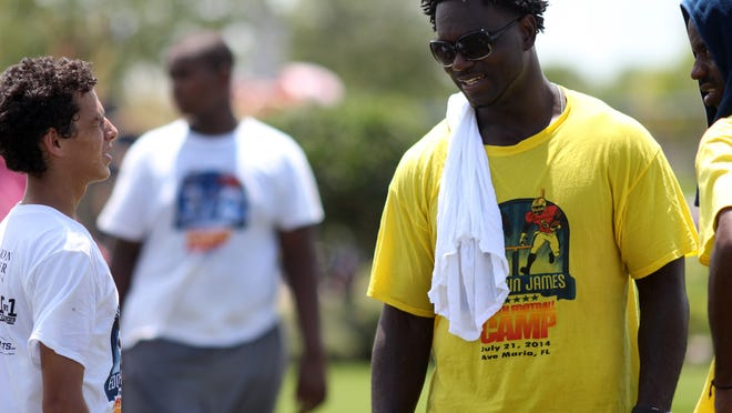 Former NFL running back Edgerrin James stops to talk with a camper Monday afternoon during his football camp at Ave Maria.