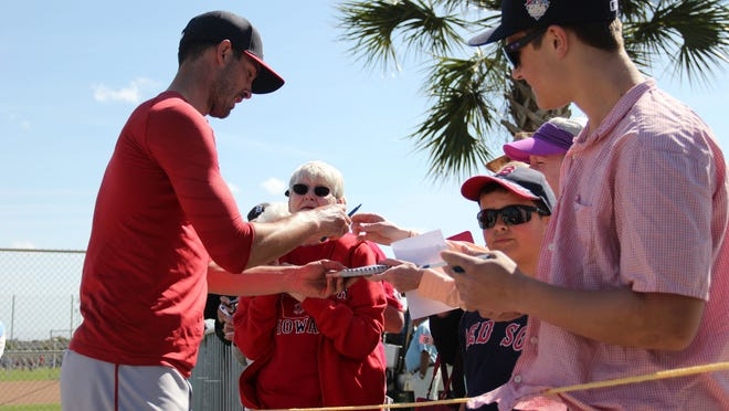 Boston Red Sox pitcher Rick Porcello signs autographs for fans after Saturday afternoon's Red Sox workout during the first official day of spring training at JetBlue Park.