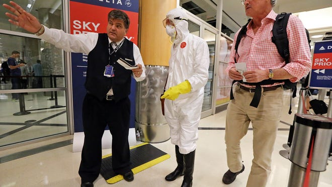 Dr. Gil Mobley of Missouri prepares to board a plane dressed in full Ebola protection gear on Oct. 2, 2014, at Hartsfield-Jackson Atlanta International Airport to protest what he sees as federal heath officials' mismanagement of the Ebola crisis. The White House announced new airport screening procedures on Wednesday, Oct. 8, 2014.