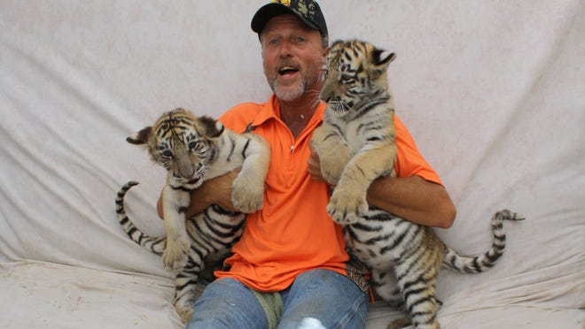 """Tim Stark, owner of Wildlife in Need Inc., hams it up with his tiger cubs Ockshay and Luush. """"It was awesome,"""" said Tyler Brumley, 7, after holding a cub on his lap."""