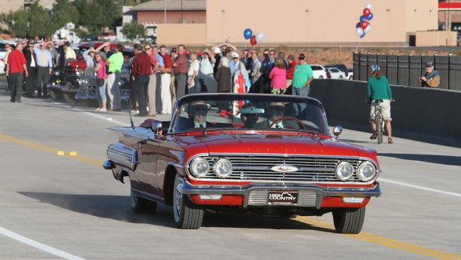 St. George Mayor Jon Pike drives other dignitaries across the new Mall Drive bridge Tuesday, Sept. 30, 2014. Classic cars for the event were provided by Utah Rep. Don Ipson.