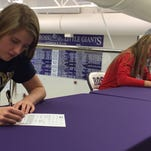Fremont Ross seniors Morgan Waggoner (left) and Meghan Moses (right) sign their National Letters of Intent to swim in college Thursday at Fremont Ross High School's Hawk-Bucci Natatorium. Waggoner will swim at Akron University while Moses will attend Rutgers University.