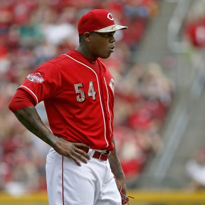 Reds closer Aroldis Chapman stands with his hand on