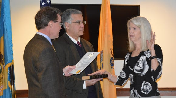 DRBA Chairman Bill Lowe (left) administers the oath of office to incoming Delaware Commissioner Crystal Carey (right) as Executive Director Scott Green holds the Bible.