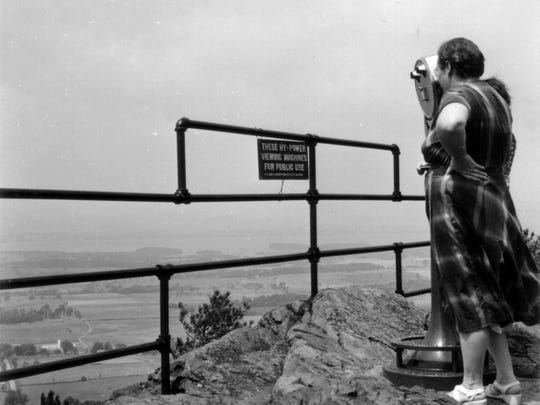 Visitors stand at the Mount Philo outlook, circa 1940s. The image was taken by Mac Derick, one of Vermont's earliest promotional photographers.