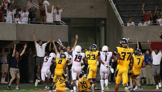 The Arizona Wildcats react after Austin Hill's game-winning touchdown catch with no time left against the Cal Bears at Arizona Stadium on Sept. 20, 2014 in Tucson, Arizona. The Wildcats 49-45.