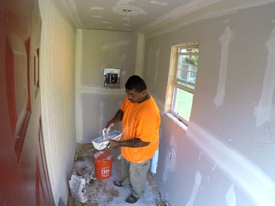 Construction worker Maurice Jones Sr. drywalls inside a micro home . A Nashville interfaith congregation exceeded its $50,000 fundraising mark last week and has spent the better part of this one building a village of eight micro homes for the homeless.