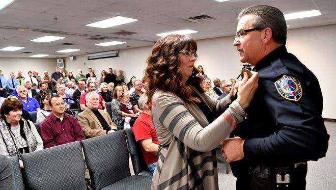 Lori Lassetter pins a new badge on her husband, Tony, during a ceremony Wednesday at the Abilene Police Department. He was promoted to lieutenant and has been with APD since 1988.