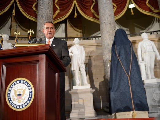 Speaker of the United States House of Representatives John Boehner prepares to pull the cover from the statue of Dr. Norman E. Borlaug during the official unveiling of the Dr. Norman E. Borlaug statue in National Statuary Hall at the U.S. Capitol.  The date would have been Dr. Borlaug's 100th birthday and is also National Agriculture Day.